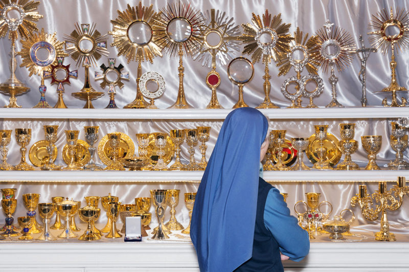 Besides Faith – A Nun Standing In Front Of Shiny Ostensoriums